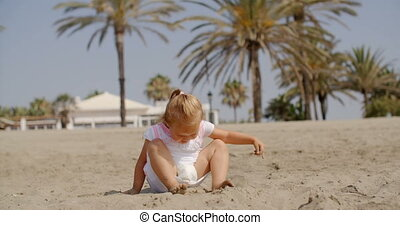 Little girl having fun a tropical beach stamping around in...