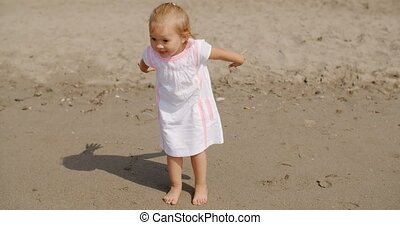 Cute little girl playing on the beach leaning towards the...