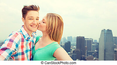 happy couple taking selfie over city background - travel,...
