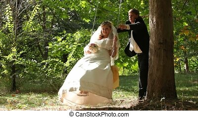 On The Swing - Groom swings his bride in the park, they kiss...