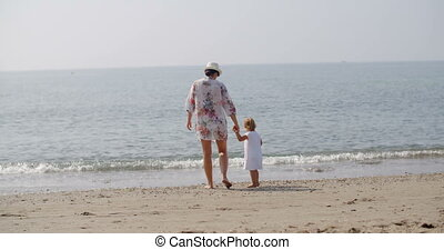 Woman Walking Hand in Hand with Child on Beach - Full Length...