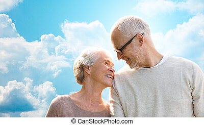 happy senior couple over blue sky and clouds