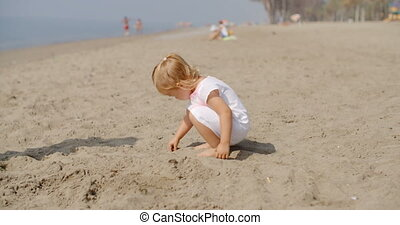 Young Child Playing on Sandy Beach - Close Up of Young Child...