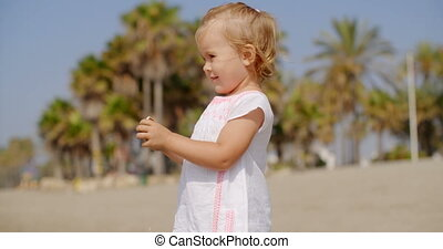 Young Blond Girl in White Dress on Tropical Beach - Close Up...