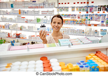 happy female customer with drug jar at pharmacy