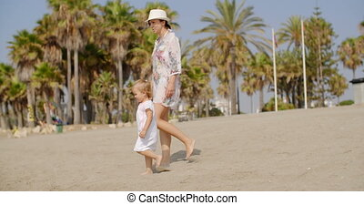 Mother walking on a beach with her small daughter - Mother...