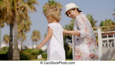 Small Girl Walking with Mother at Tropical Park among Palm...