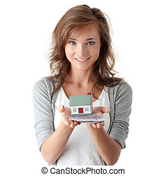 Woman holding euros bills and house model - Beautiful young...