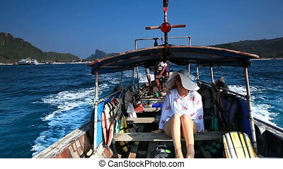 Young woman in the boat leaving Phi Phi harbor on the way to...