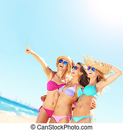 Group of women pointing at something on the beach