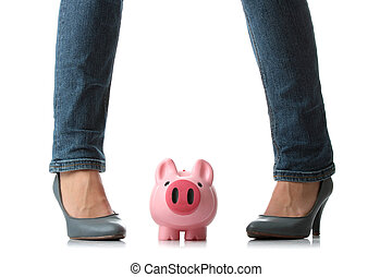 Young woman about to smash piggy bank with her legto get at...