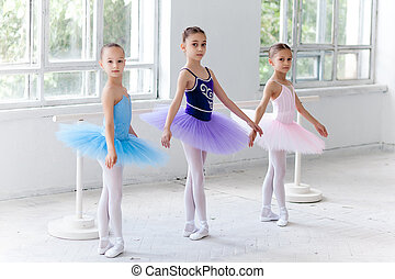 Three little ballet girls sitting in tutu and posing...