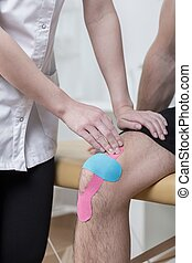 Kinesiology taping for painful knee - Close-up of...