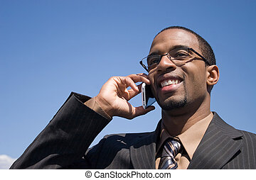Cell Phone Service - A young business man talking on his...