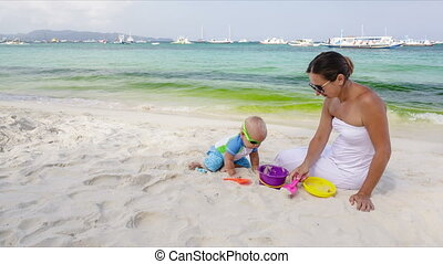Baby and mother on the beach - Baby and mother playing with...