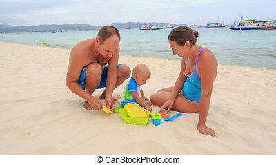 Family on the beach - Parents and baby playing together on...
