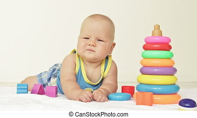Baby crashes toy pyramid - Baby boy crashes toy pyramid on...