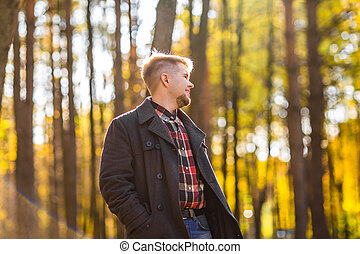 man wearing a coat in the autumn park