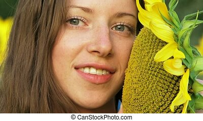 Sunflowers - Close-up. Beautiful girl next to sunflowers.