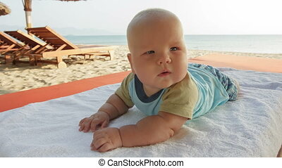 Baby boy on the sunbed - Baby boy looks to the camera...