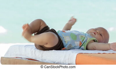 Baby boy plays with his feet on the sunbed