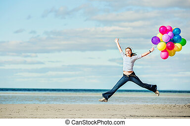 Beautiful girl jumps on the beach while holding colored...