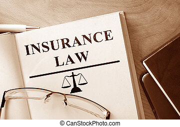 Insurance Law - Book with words Insurance Law and glasses.
