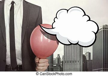 Empty speech bubble with businessman holding balloon on...