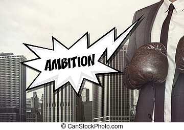 Ambition text with businessman wearing boxing gloves on...