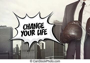 Change your life text with businessman wearing boxing gloves...