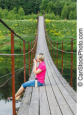 Pedestrian suspension bridge of steel - blonde girl with...