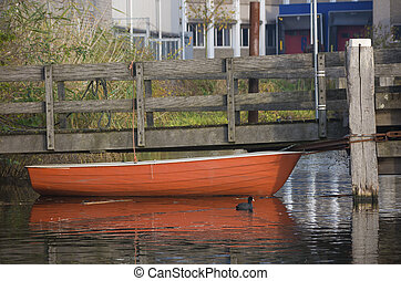 red rowing boat moored at a pier