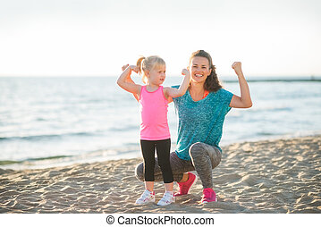 Young mother and daughter in fitness gear on beach flexing...