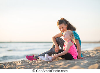 Happy young mother and daughter talking and sitting on the...