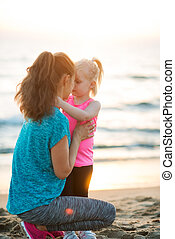 Fit young mother and daughter on beach giving Eskimo kisses...