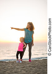 Fit young mother pointing into distance for daughter on...