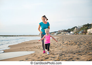 Fit, happy mother running behind young daughter on the beach...