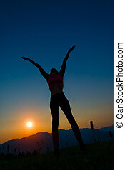 Silhouette of woman at sunset in the mountains