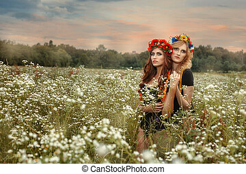 Two girls standing in an embrace the field.