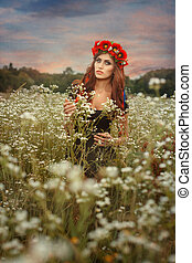 Beautiful girl with a wreath on her head. She stands in a...