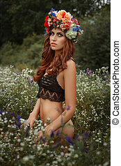 Beautiful girl among wildflowers On her head a wreath