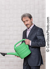 Mature businessman with watering pot - Picture of mature...