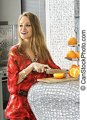 blonde in modern kitchen cuts oranges - happy beautiful...