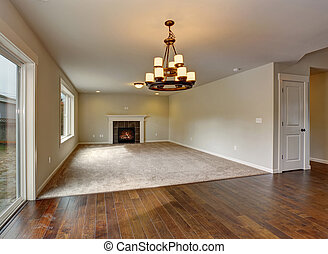 Large unfurnished living room with fireplace.