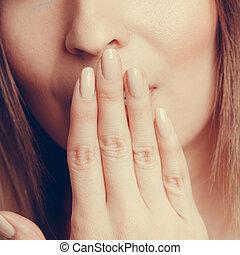 Shy speechless human covering mouth with hand. - Closeup of...