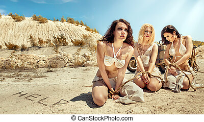 Three sexy tied slave women on the desert background