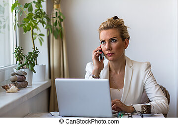 Young business woman talking on phone sitting at a desk with...