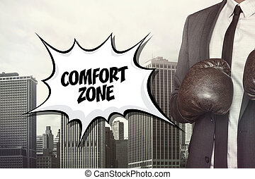 Comfort zone text with businessman wearing boxing gloves on...