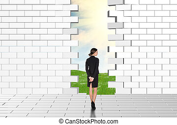 Beautiful businesswomen watching dilapidated brick wall -...