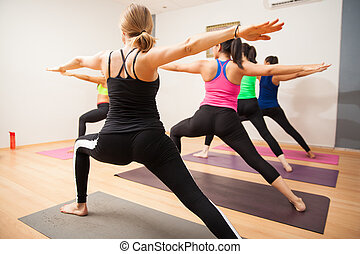 Warrior pose in yoga class - Student point of view of a yoga...